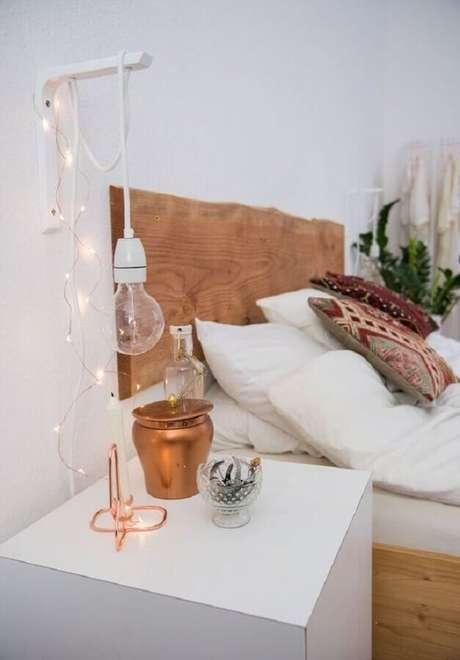 55. Quarto branco decorado com cabeceira de madeira rústica e luminária de parede simples – Foto: Jeito de Casa