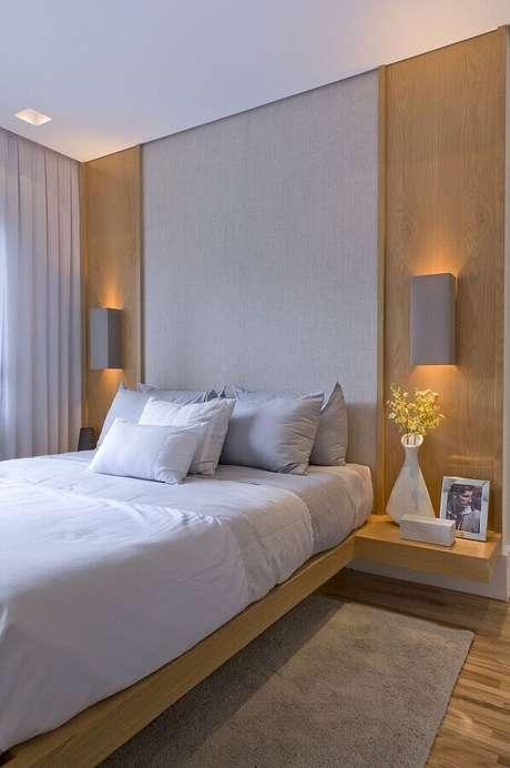 24. Decoração de quarto de casal com luminária de parede arandela e cabeceira cinza planejada – Foto: Débora Aguiar