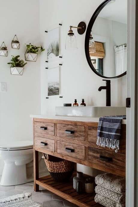 21. Luminária de parede de vidro para decoração de banheiro com gabinete de madeira e espelho redondo – Foto: Decoholic