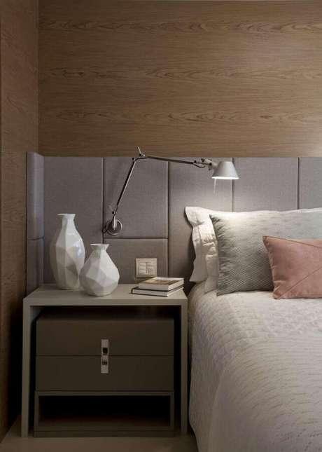 8. Luminária articulada de parede para quarto decorado com cabeceira cinza e parede com revestimento de madeira – Foto: Jeito de Casa