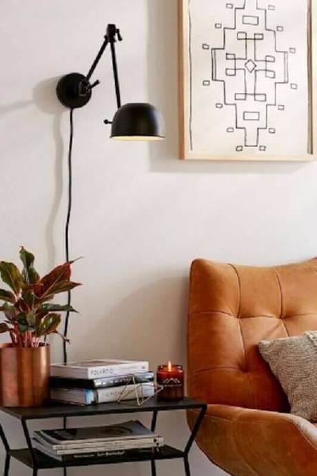 39. Decoração com luminária de parede sala de estar com poltrona marrom – Foto: The Everygirl