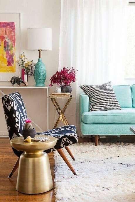 11. Sala decorada com tapete shaggy e poltrona pé palito preto e branca. Fonte: Decoist