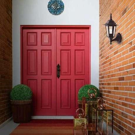 5. Luminária antiga de parede para decoração de fachada com porta vermelha – Foto: Pinterest