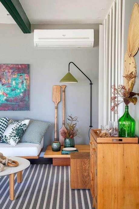 52. Luminária de parede para sala cinza moderna decorada com tapete listrado – Foto: Casa de Valentina
