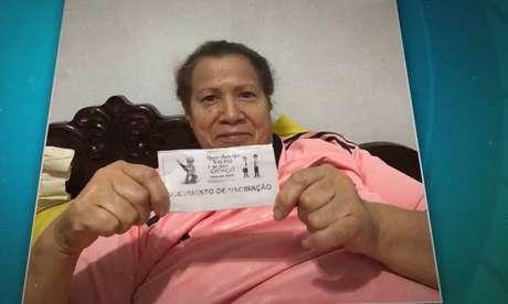 Dona Loiva mostra carteirinha de vacinação após ser vacinada (Foto: Reprodução/Globo)