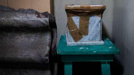 Num canto da garagem da casa de Elsa Maldonado está a urna com as cinzas de um estranho