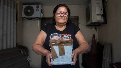 Elsa Maldonado reza às cinzas que permanecem nesta urna todos os dias antes de sair de casa