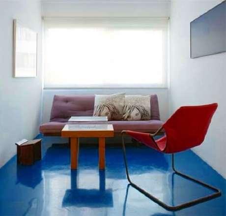 29. O piso queimado colorido em tom azul é o grande destaque dessa sala de estar. Fonte: Pinterest