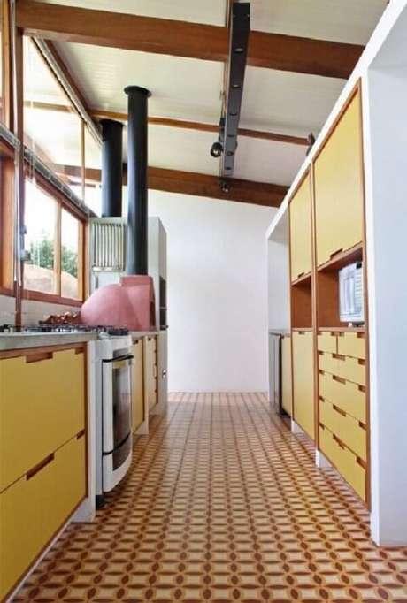 48. Cozinha com armários amarelos e piso coloridos em tons terrosos. Fonte: Zehbra Arquitetura