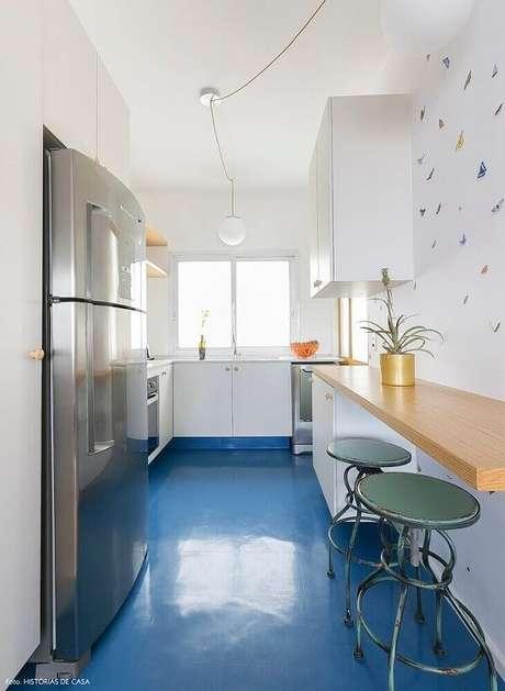 26. Piso colorido cozinha azul, armários brancos e bancada de madeira formam uma linda composição. Fonte: Histórias de Casa