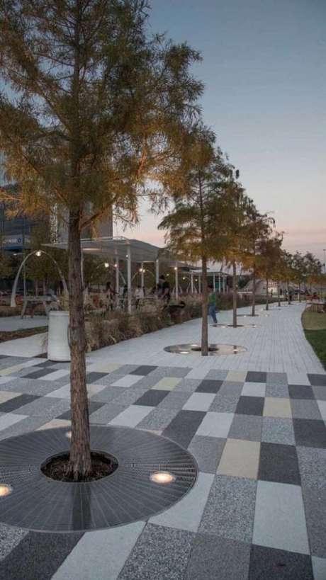 12. Piso intertravado colorido em tons neutros decoram a área externa com canteiros com árvores. Fonte: Pinterest