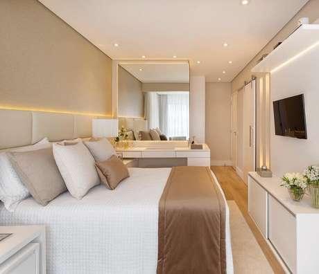 37. Painel de TV para decoração de quarto bege e branco com cabeceira estofada – Foto: Decor Salteado