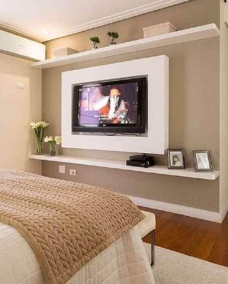 38. Cor bege para quarto de casal decorado com painel de TV – Foto: Pinterest