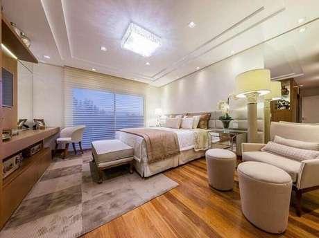28. Decoração de quarto bege amplo com poltrona confortável e painel para TV – Foto: Pinterest
