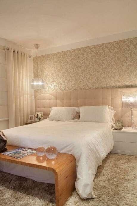 40. Papel de parede para quarto bege decorado com cabeceira estofada e banco de madeira – Foto: ArchiZine
