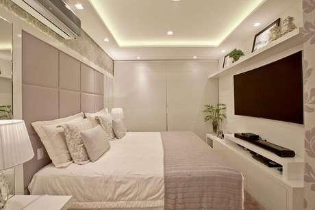 24. Decoração de quarto de casal bege e branco com painel de TV – Foto: Arq MBaptista