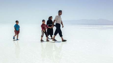 Família caminha pela crosta de sal seca e dura do outrora Lago Urmia, no Irã