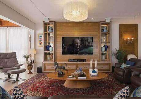 45. Modelo de tapete persa para decoração de sala de TV com poltronas de couro e mesa de centro redonda – Foto: Revista Sua Casa