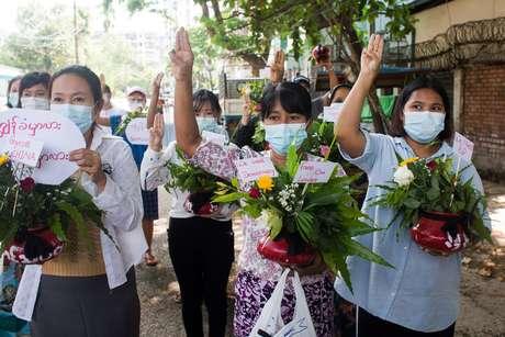 Mulheres carregam vasos de flores durante protesto contra golpe militar em Mianmar 13/04/2021 REUTERS/Stringer