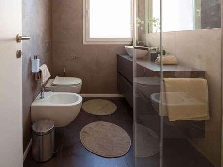17. Decoração de banheiro com modelos de tapetes redondos e parede de cimento queimado – Foto: Istock