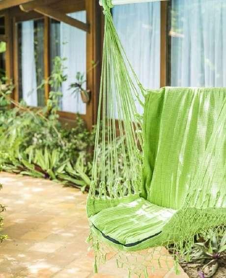 41. O tom verde da cadeira de balanço rede se mistura com as plantas do jardim. Fonte: Teixeira Redes
