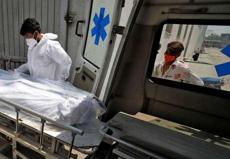 Profissional de saúde coloca corpo de homem que morreu de Covid-19 em ambulância em hospital de Ahmedabad, na Índia 14/04/2021 REUTERS/Amit Dave