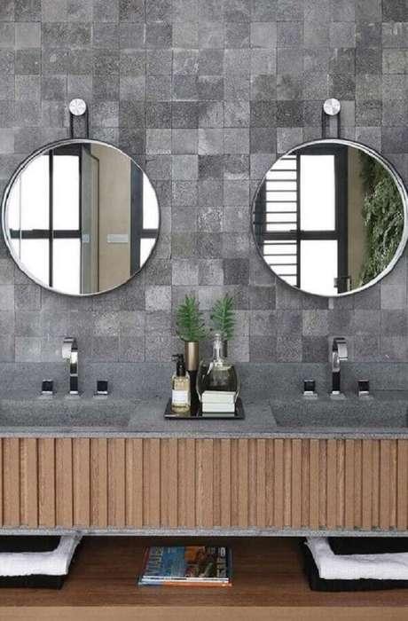 28. Decoração de banheiro com revestimento cinza e espelho redondo – Foto: Quattrino Arquitetura