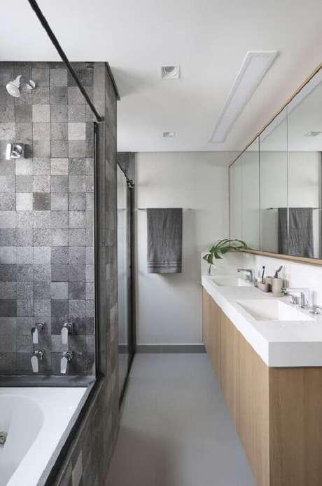 55. Revestimento cinza quadriculado para banheiro decorado com gabinete de madeira – Foto: Quattrino Arquitetura