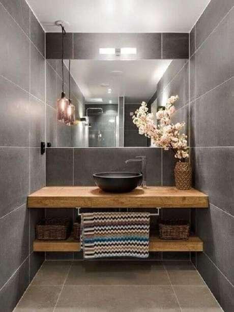 51. Revestimento cinza para banheiro pequeno decorado com bancada de madeira e cuba preta – Foto: Freshideen