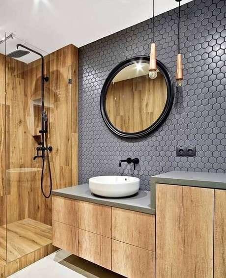 26. Banheiro amadeirado moderno decorado com espelho redondo e revestimento hexagonal cinza – Foto: Jeito de Casa