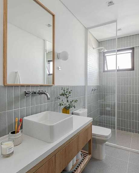 9. Revestimento cinza para banheiro branco decorado com gabinete de madeira – Foto: Duda Senna