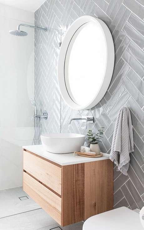 47. Revestimento cinza claro para banheiro clean decorado com gabinete suspenso de madeira – Foto: Pinterest