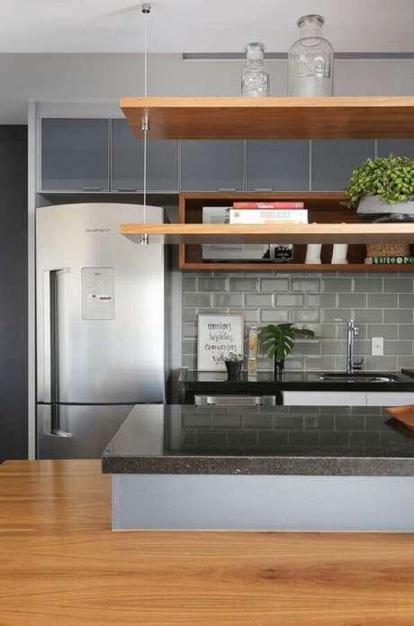 33. Revestimento metro cinza para decoração de cozinha planejada com prateleira suspensa de madeira – Foto: Jeito de Casa