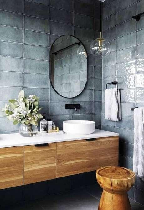 17. Revestimento cinza par banheiro moderno decorado com gabinete de madeira e espelho oval – Foto: Freshideen
