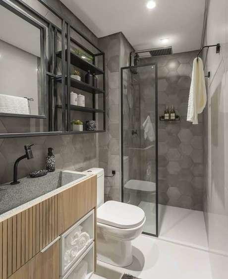 30. Decoração de banheiro moderno com gabinete de madeira e revestimento cinza hexagonal – Foto: Jeito de Casa