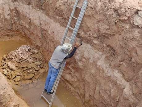 O biólogo Leonardo Paschoa escava fragmentos de fósseis de dinossauros achados durante obra em rodovia, no interior de São Paulo
