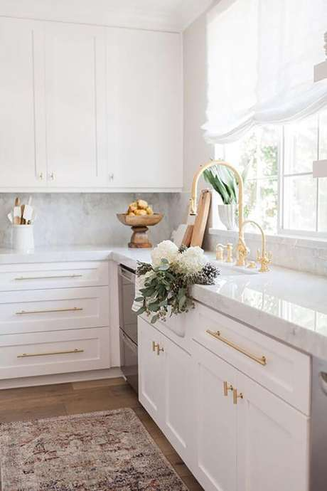38. Bancada de cozinha branca com armários da mesma cor e torneira dourada gourmet – Foto Hurd and Honey