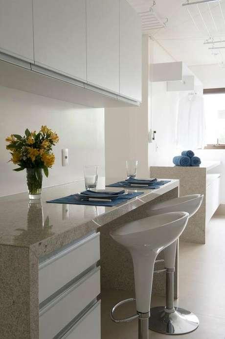 37. Bancada de cozinha em granito bege com bancos brancos para cafe da manhã – Foto Casa Vogue