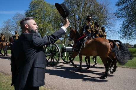 Uma pessoa saúda parte da cavalaria que passa