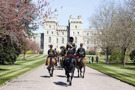 membros da cavalaria real com uniformes cavalgam até o castelo de Windsor