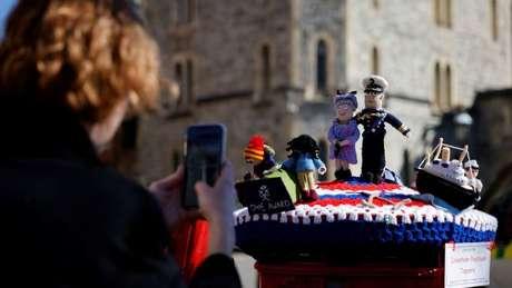 Mulher tira foto de bonequinhos de crochê feitos em homenagem à rainha e ao príncipe