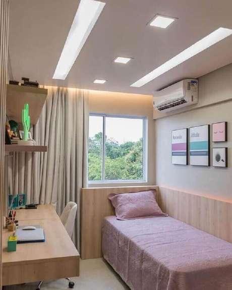 43. Mesa de estudo para quarto de solteiro feminino decorado com cabeceira de madeira – Foto: Jeito de Casa