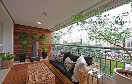 63. Varanda ampla decorada com um lindo sofá de vime e vasos de plantas. Fonte: Revista Viva Decora 2