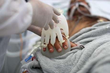 """Semei Araújo Cunha, da equipe de enfermagem, encaixa o que chama de """"mãozinha do amor"""" em paciente com Covid-19, em UPA de São Carlos (SP) 16/04/2021 REUTERS/Amanda Perobelli"""