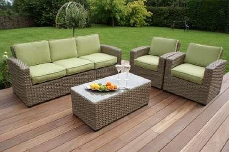 18. As almofadas em tom verde do sofá de vime se misturam com a grama do jardim. Fonte: Pinterest