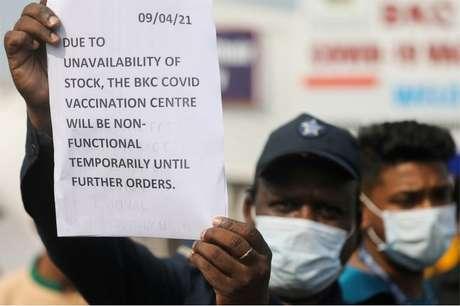 Um guarda segura um aviso para informar às pessoas sobre a escassez de suprimentos de vacina contra o coronavírus