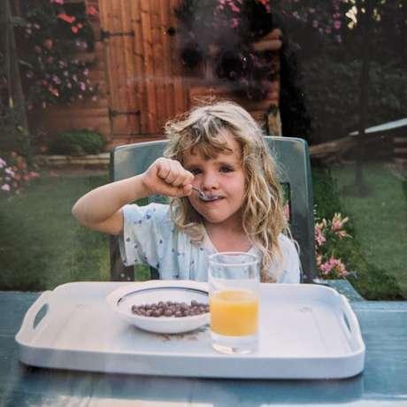 Loretta ainda criança comendo café da manhã de Mavis no jardim