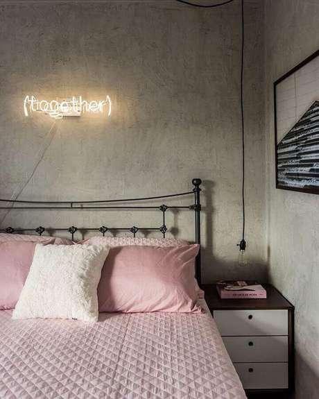17. A parece de cimento queimado junto com a cama de ferro trazem um ar urbano para o quarto de mulher decorado – Foto: Apartamento 33