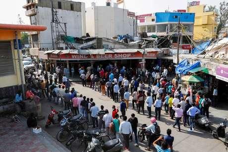 Pessoas fazem fila em frente a loja de bebidas em Nova Délhi depois de governo local decretar seis dias de lockdown para frear disseminação do coronavírus 19/04/2021 REUTERS/Adnan Abidi