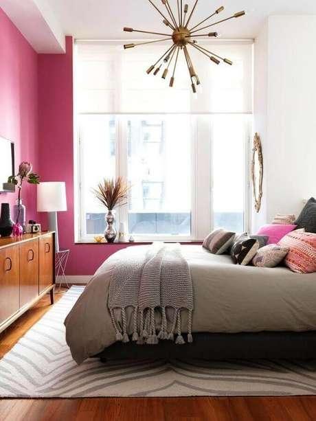 10. Parede rosa para decoração de quarto de mulher com lustre moderno e cômoda de madeira – Foto: Brit+Co